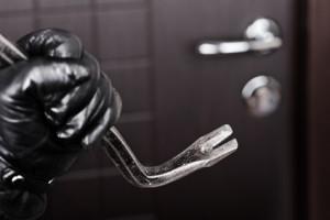 Einbrecher der mit Brecheisen auf Tür zu geht