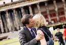 Mann begrüßt Frau herzlich mit einem Kuss auf die Wange