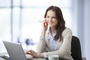 Junge Frau surft im internet mit Handy am Ohr
