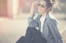 Fröhliche junge frau mit Sonnenbrille und Denim-Look